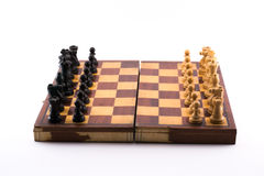 Chess board with black and white figurines on a white background Stock Photo
