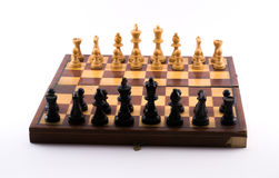 Chess board with black and white figurines on a white background.  Royalty Free Stock Photography