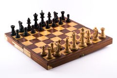 Chess board with black and white figurines on a white background.  Stock Photos