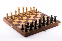 Chess board with black and white figurines on a white background Stock Photography
