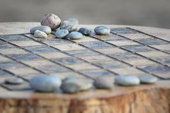 Chess Board Carved Out Of Stump With Stone Pieces. A chess board carved into a stump, accented by natural, smooth stone game pieces royalty free stock images