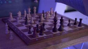 Chess Board With Chess. Caucasian white male hands at evening dark night scene with camera movement shot in slow motion with dynamic color of light stock video