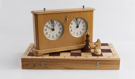 Chess board and chess clock on a white background Royalty Free Stock Images