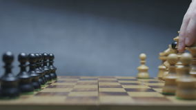 Two players prepring chess pieces before the game. Chessboard with classic wood pieces. Gradient gray background. Shot on RED Epic stock video footage
