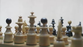 Two players preparing chess pieces before the game. Chess board with classic wood pieces. White background. Shot on RED Epic stock video footage