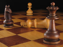Chess Board Conquest. Chess board still life of a defeated king and triumphant queen and knight against a black background royalty free stock photography