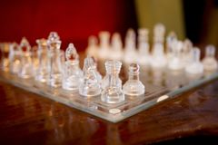 Chess board and crystal chess on wooden floor stock photos