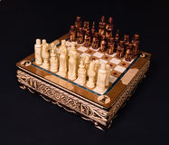 Chess board with figures. On a black background Stock Images