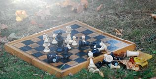 chess board and figures on a autumn grass royalty free stock photography