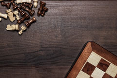 Chess board and figures over woden background Stock Images