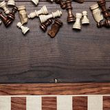 Chess board and figures on woden background Royalty Free Stock Photo