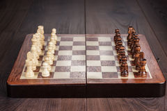 Chess board with figures on wooden table Royalty Free Stock Photos