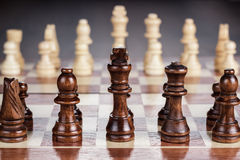 Chess board with figures on the wooden table Stock Photos