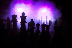 Chess board game concept of business ideas and competition. Chess figures on a dark background with smoke and fog. Selective focus stock photos