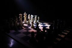 Chess board game concept of business ideas and competition. Chess figures on a dark background with smoke and fog. Selective focus royalty free stock photo
