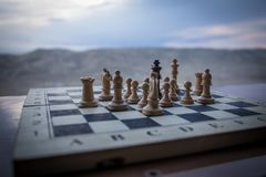 Chess board game concept of business ideas and competition. Chess figures on a chessboard. Outdoor sunset background. Selective focus royalty free stock images