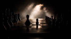 Chess board game concept of business ideas and competition. Chess figures on a dark background with smoke and fog. Selective focus stock images