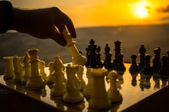 Chess board game concept of business ideas and competition and strategy ideas. Chess figures on a chessboard outdoor sunset backgr. Ound. Selective focus royalty free stock image