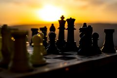 Chess board game concept of business ideas and competition and strategy ideas. Chess figures on a chessboard outdoor sunset backgr. Ound. Selective focus stock photography
