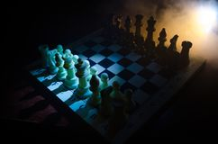 Chess board game concept of business ideas and competition and strategy ideas concep. Chess figures on a dark background with smok. E and fog. Selective focus Royalty Free Stock Image