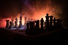 Chess board game concept of business ideas and competition and strategy ideas concep. Chess figures on a dark background with smok stock images