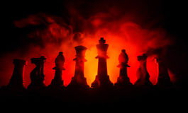 chess board game concept of business ideas and competition and strategy ideas concep. Chess figures on a dark background with smok Royalty Free Stock Photo