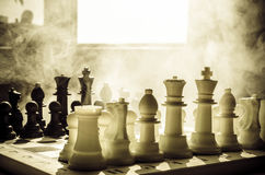 chess board game concept of business ideas and competition and strategy ideas concep. Chess figures on a dark background with smok Royalty Free Stock Photos
