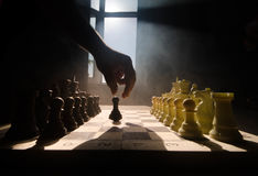Chess board game concept of business ideas and competition and strategy ideas concep. Chess figures on a dark background with smok. E and fog. Selective focus royalty free stock images