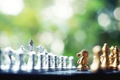 Chess board game. Fighting between silver and golden team. Business competitive and strategy planning concept. stock images