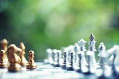 Chess board game. Fighting between silver and golden team. Business competitive and strategy planning concept. stock photo