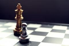 Chess board game. The pawn stand against a king. Refer to a person with courage and ambitious concept. Focus on pawn. Copy space for text stock photos