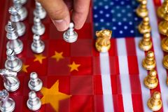 Chess board game pieces on USA and China flag background, trade war tension situation concept royalty free stock image
