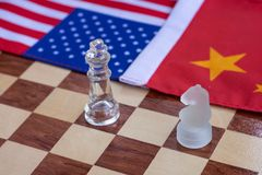 Chess board game pieces on USA and China flag background, trade war tension situation concept. Copy space, group, success, teamwork, trapped, surrounding stock photo