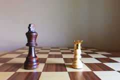 White pawn wearing golden crown stand confront with Black King. Business leadership concept. The true winner. Chess board game. White pawn wearing golden crown stock photography