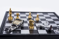 Chess Board isolated on white background. Golden and silver figures with hand watch.  royalty free stock photography