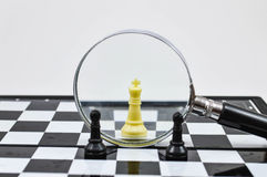 Chess board with magnifying glass Stock Images