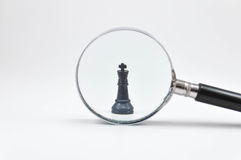 Chess board with magnifying glass Royalty Free Stock Photo