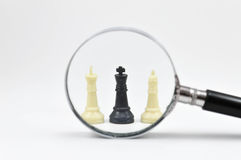 Chess board with magnifying glass Royalty Free Stock Photography