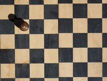Chess board with a one black pawn. On a white square royalty free stock image