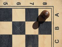 Chess board with a one black pawn. On a white square royalty free stock photo