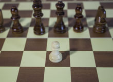 Chess Board - Pawn coin facing powerful enemies. Pawn coin facing powerful enemies in chess board royalty free stock image