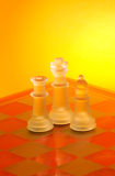 Chess board. Chess pieces on board in yellow and orange backlight Royalty Free Stock Image