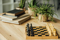 Chess board set for a new game on the table with books and potted plants Stock Image