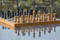 Chess board on a table. Chess board with reflection on a glass table in a garden royalty free stock image