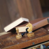Chess And Books. Some chess pieces in focus and books in the blurred background, concept of leisure games. Macro shot with selective focus Stock Image