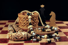 Chess, box from birch bark and a necklace. On a chessboard there is a casket from birch bark and a beads from an ivory and handmade chessman Stock Image