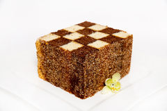 Chess cake. On a white plate which costs on a table, lie flowers nearby royalty free stock images