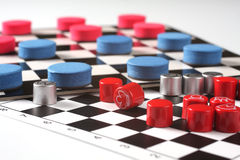 Chess and checkers. Red and blue chess and checkers withe check board Royalty Free Stock Images