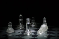 Chess checkmate. Checkmate by clear glass queen.  Light is trying to light only the queen as the main focus Stock Image