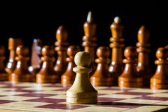 Chess on a chess board. White pawn and black chess pieces on background Royalty Free Stock Images